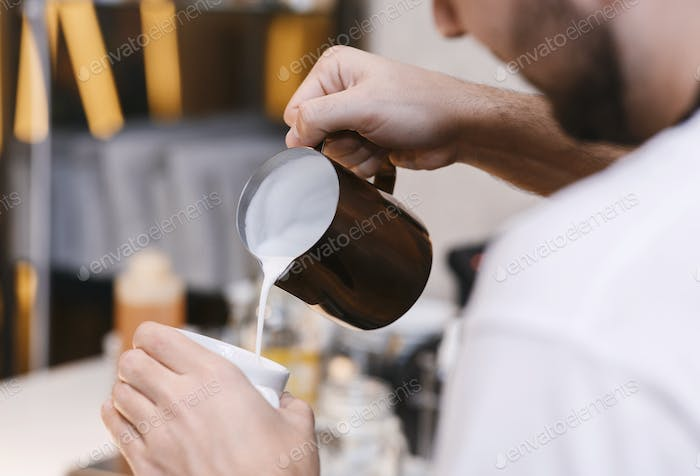Unrecognizable Barista Making Cappuccino Adding Milk In Cup In Cafeteria