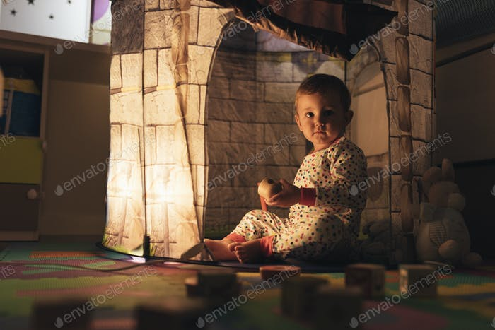 Little boy playing into castle toy at home.