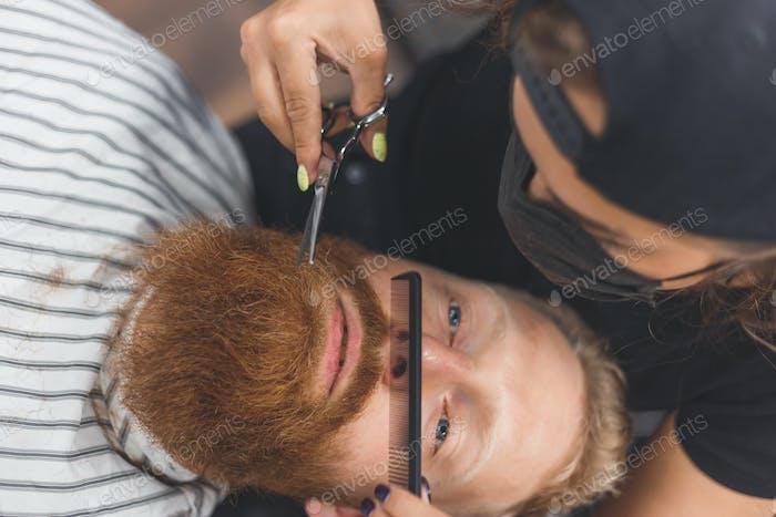 Мужчина в парикмахерской. Женщина-парикмахер обрезает усы. Парикмахер в маске.