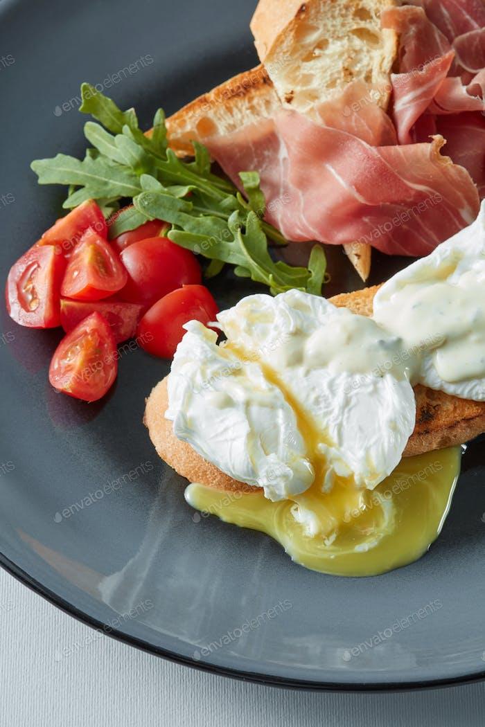 Eier Benedikt mit Speck, Toast und Salat.