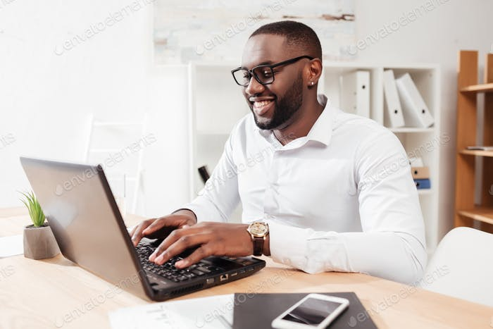 Smiling African American businessman in white shirt and eyewear sitting and working on his laptop