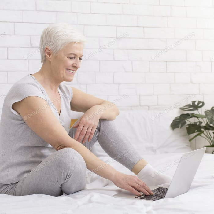 Cheerful senior lady enjoying internet on laptop at home