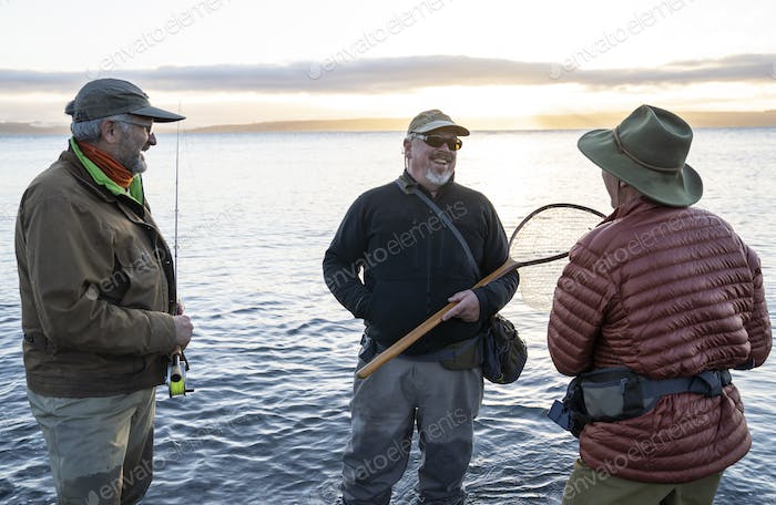 Two fly fisherman talk wtih their guide about new tecnhiques while fly fishing for searun coastal