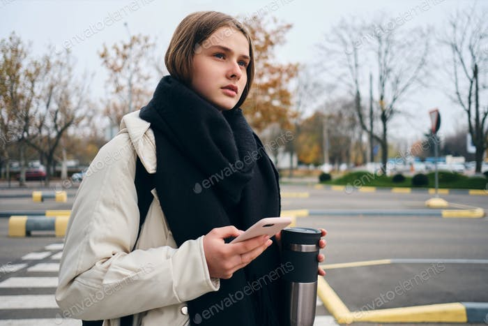 Beautiful casual girl with cellphone thoughtfully looking away