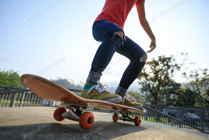 Woman skateboarder skateboarding at skatepark