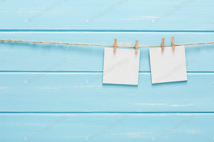 White blank cards on rope, blue wooden background
