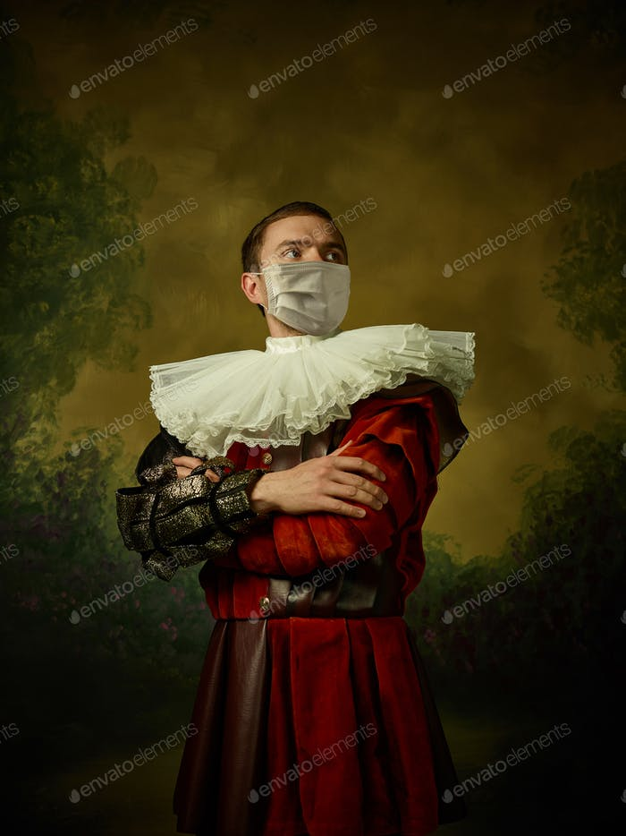 Young man as a medieval knight on dark background wearing protective mask against coronavirus
