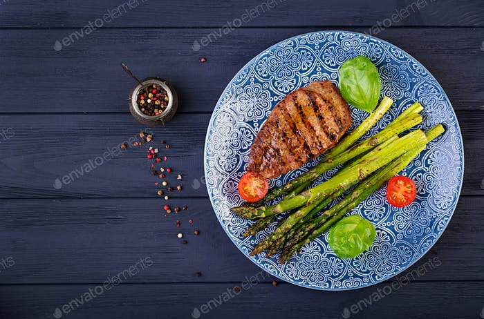 Barbecue grilled beef steak meat with asparagus and tomato. Top view