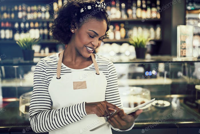 Young African entrepeneur standing in her cafe using a tablet