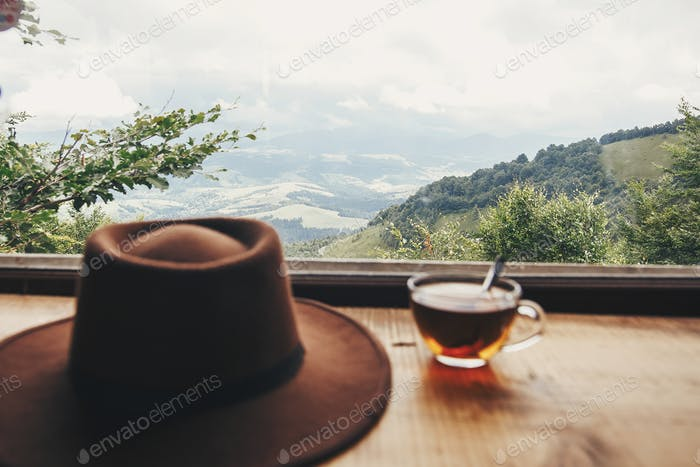hipster hat and tea in glass on wooden table at window light