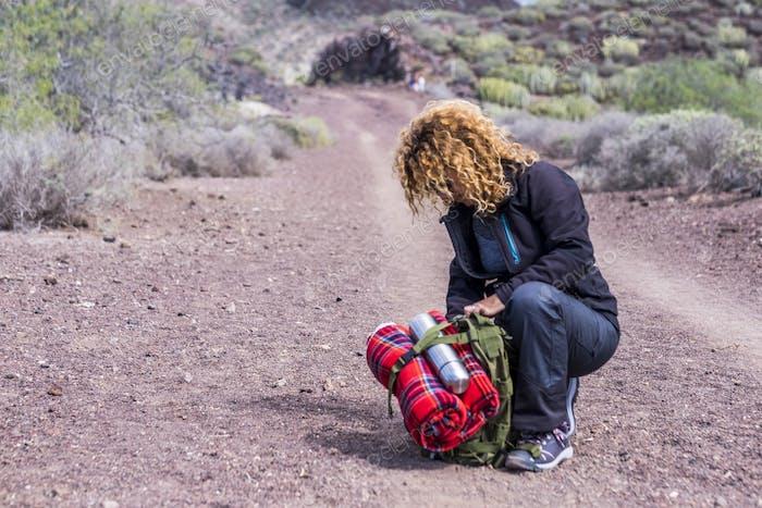 Спортивная женщина с оборудованием для проверки рюкзака во время треккинговой экспедиции