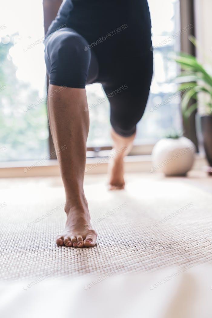 Japanische Frau, die Yoga mit Hilfe von Personal Trainer