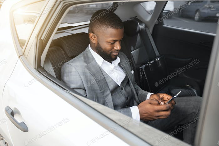Happy african businessman using mobile phone while sitting in taxi