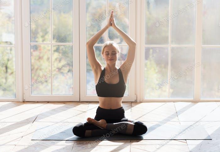 Still yoga girl meditating in sun lights at home
