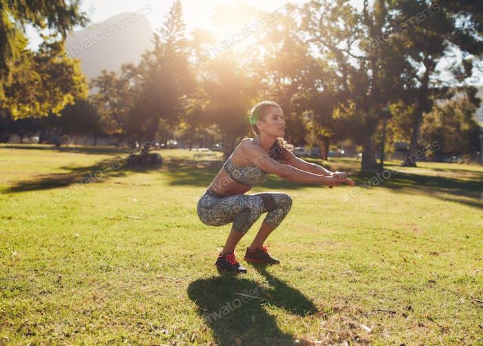 fit junge Frau tun hocken in park