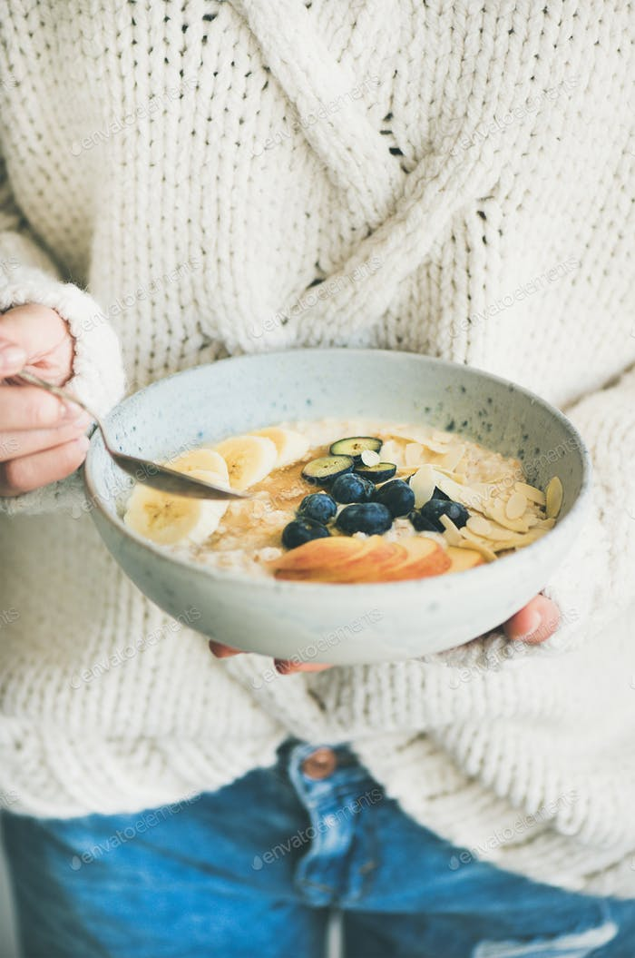 Woman in jeans and sweater eating oatmeal porriage