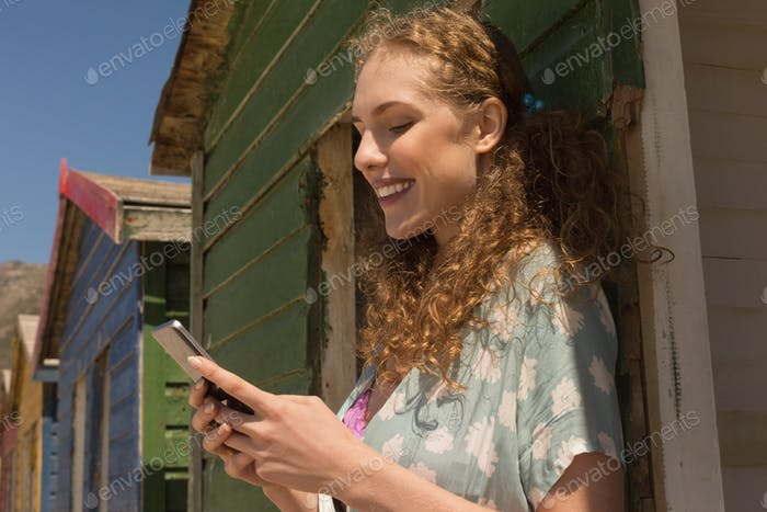 Side view of happy gorgeous young woman using mobile phone at beach hut. She is smiling