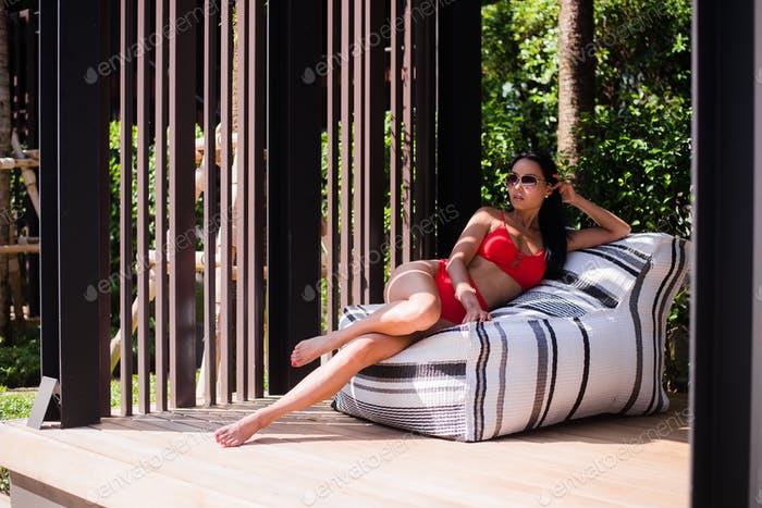 Attractive young woman in a bikini reclines back on a lounge chair next to a swimming pool.