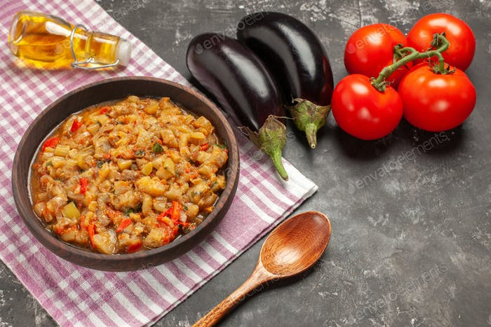 top view roasted eggplant salad in bowl wooden spoon tomatoes eggplants oil bottle on dark