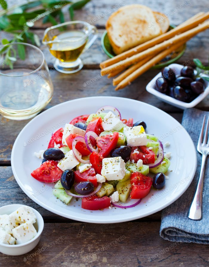 Greek salad. Fresh vegetables, feta cheese and black olives with white wine.