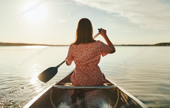 Young woman paddling her canoe on a tranquil lake
