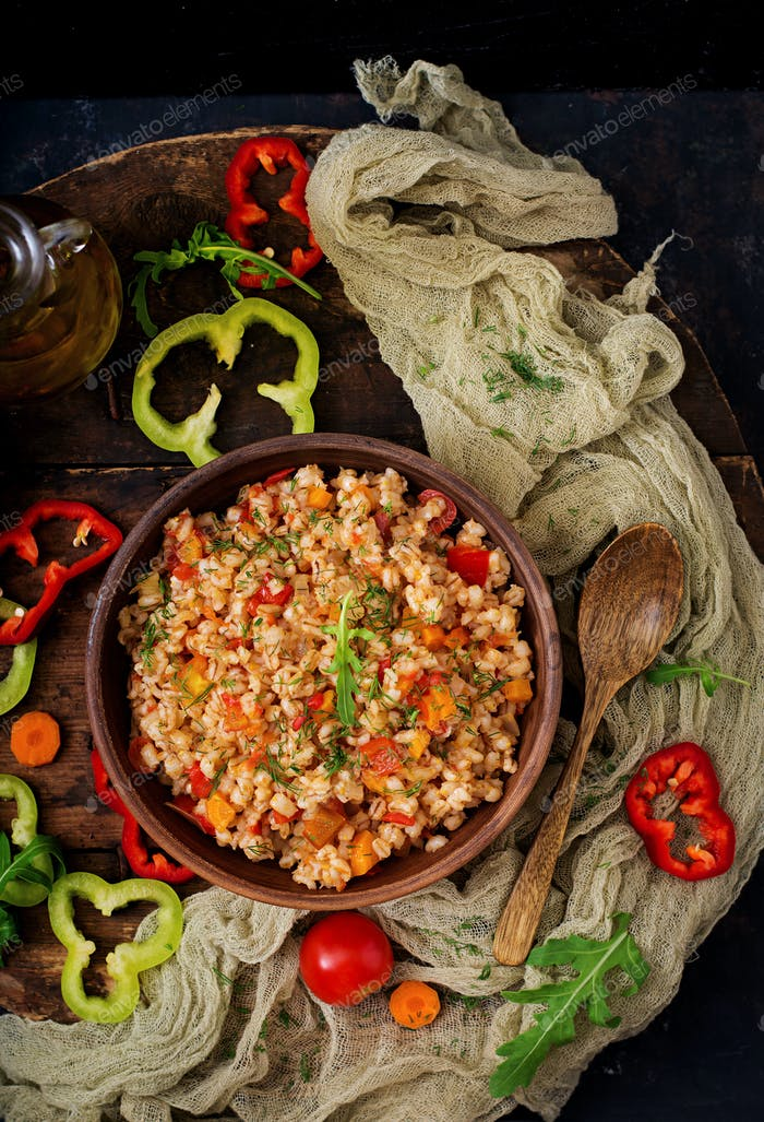 Vegetarian crumbly pearl barley porridge with vegetables  in a dark background. Flat lay. Top view
