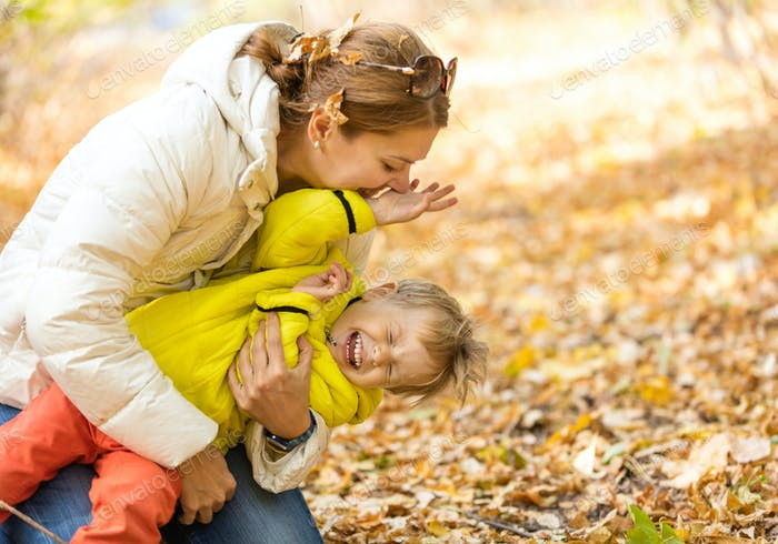 Happy woman and her little son having fun in autumn park