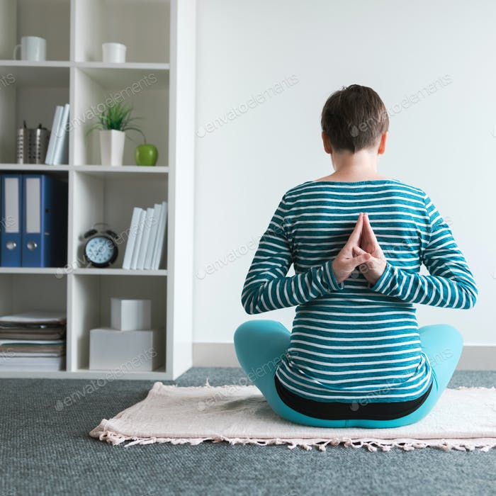Pregnant woman practicing yoga exercise at home.