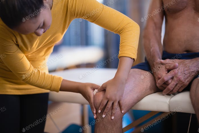 Female therapist massaging knee of senior male patient sitting on bed