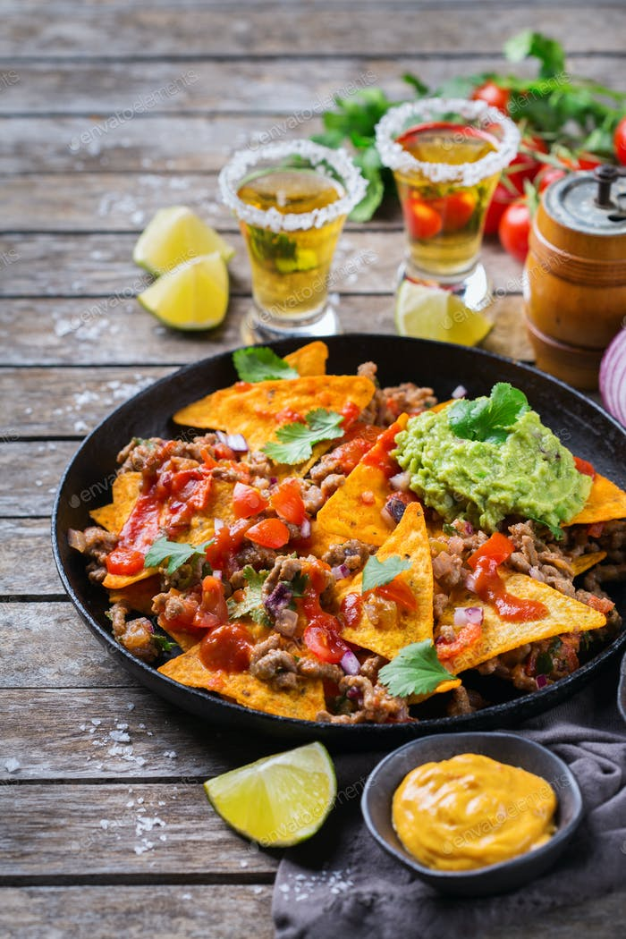 Chips nachos with beef, guacamole, chili, cheese salsa, tequila