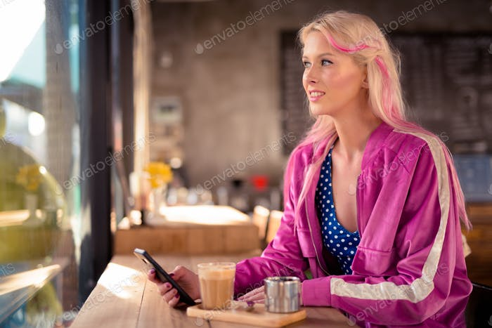 Happy young beautiful blonde woman thinking while using phone at the coffee shop