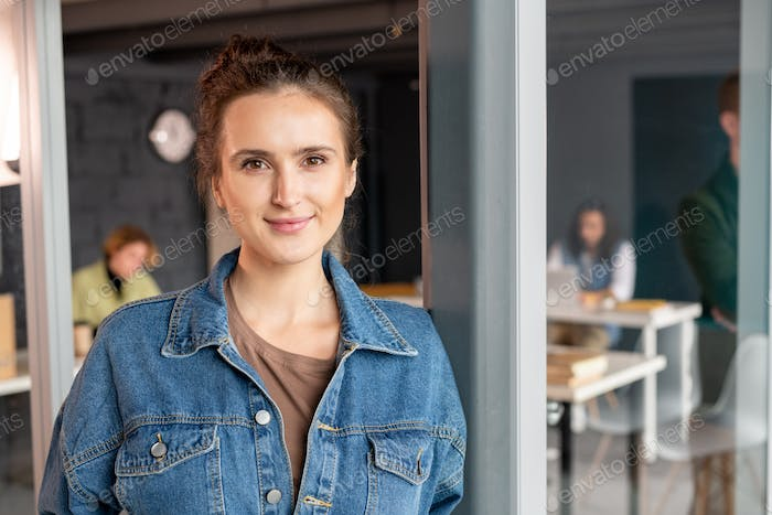 Young successful female office manager in denim shirt standing by open door