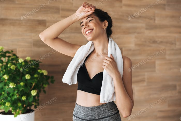 Smiling young sportsgirl standing with towel