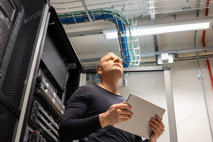 Male IT Professional Holding Digital Tablet Planning Changes in Datacenter