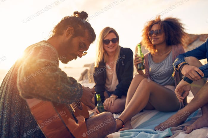 Hipster playing guitar for friends at the beach