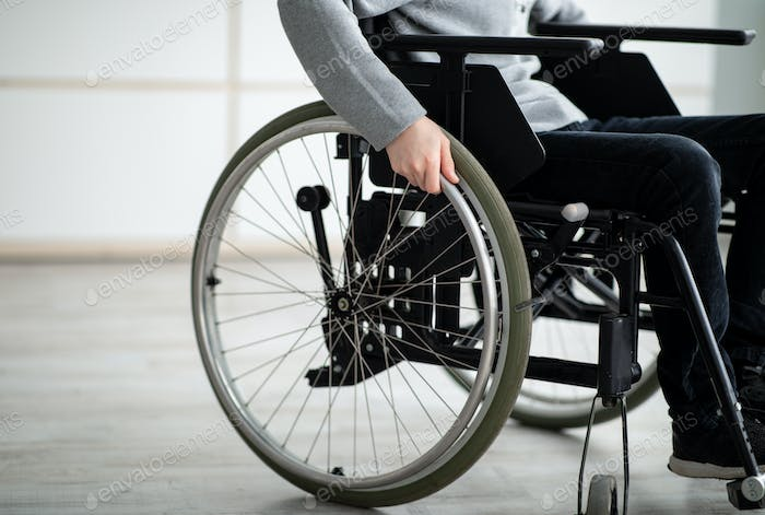 Cropped view of impaired teen boy sitting in wheelchair at home, copy space. Disability in