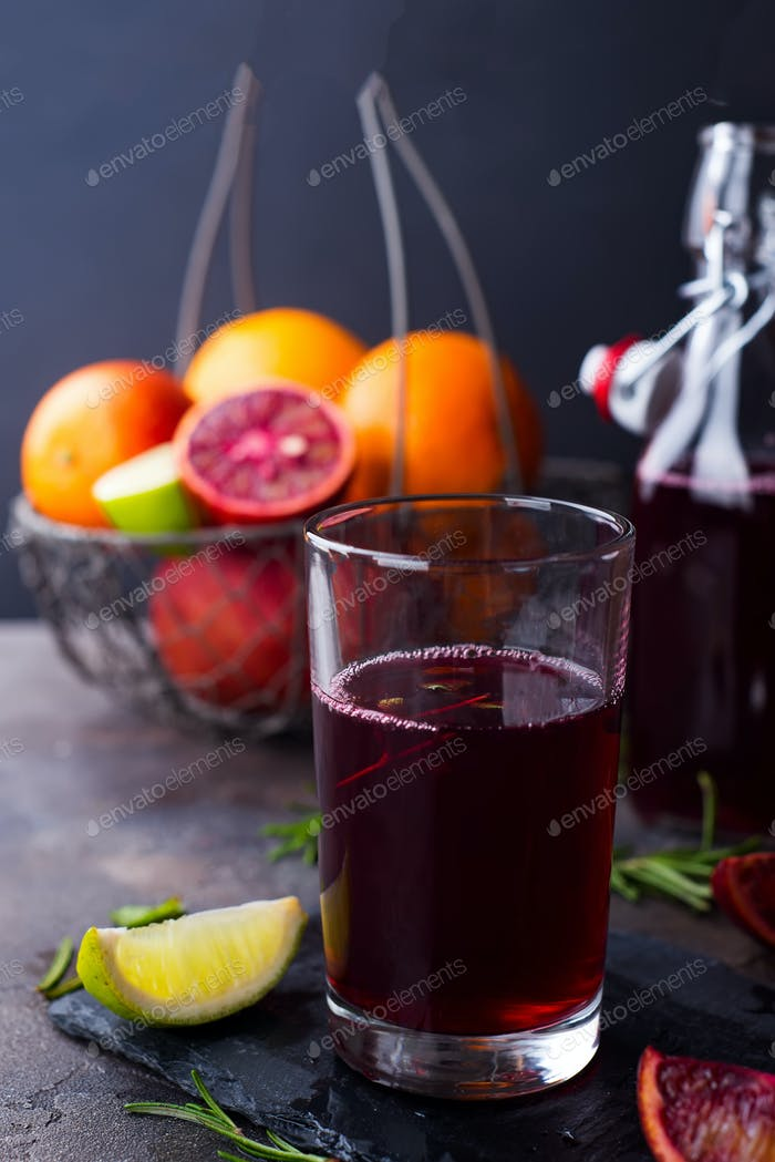 Summer berry juice in a glass with citrus on stone background