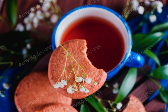 Close-up of a teacup with oatmeal cookies and spring gypsophila flowers on a warm wooden background