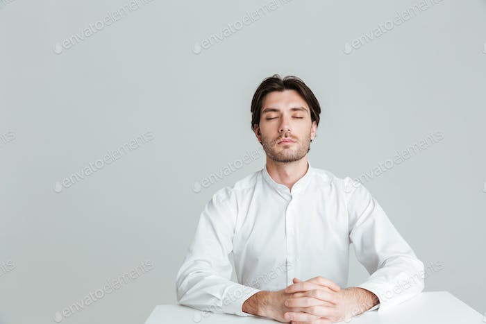 Relaxed man sitting at the table with eyes closed