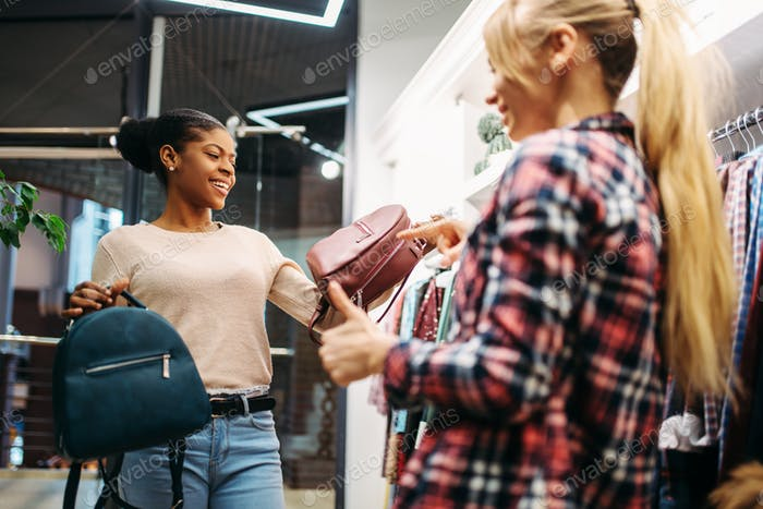 Two females choosing bags in shop, shopping