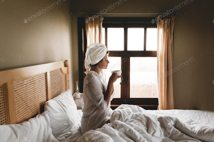 Beautiful happy young woman drinking coffee or tea in bed