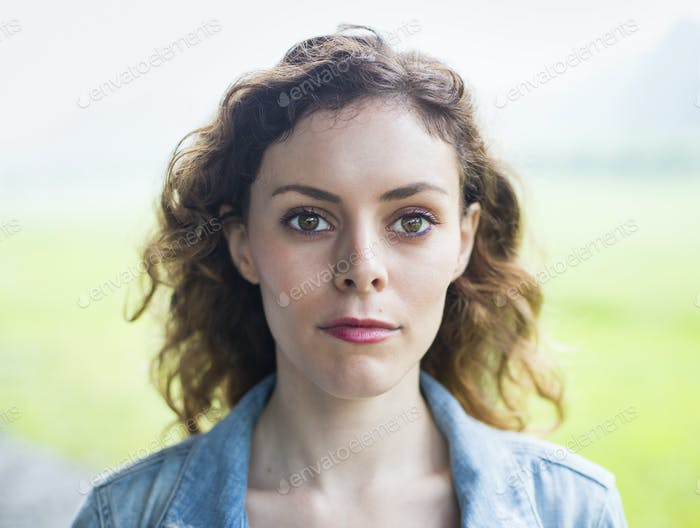 A young woman in a rural landscape, with windblown curly hair.