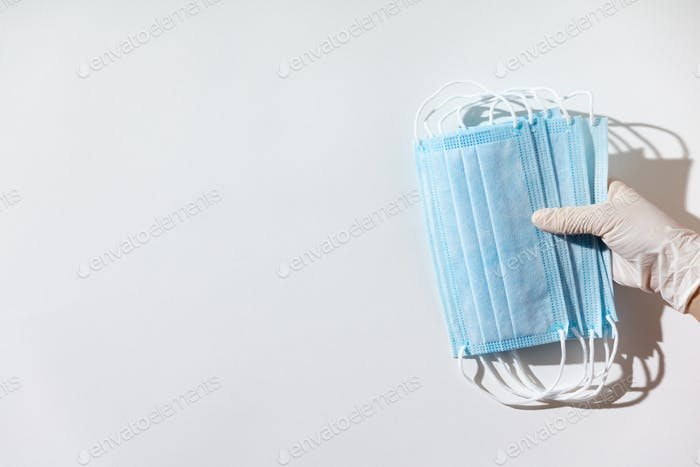 Woman hands in latex gloves holding facial medical masks, white background, close up