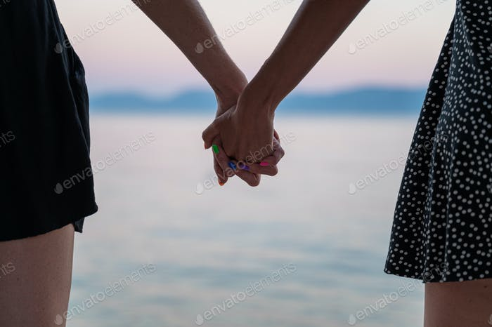 Closeup view of lesbian gay couple holding hands