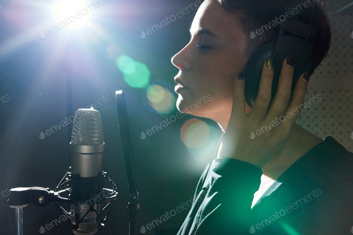 Stylish woman recording song in studio