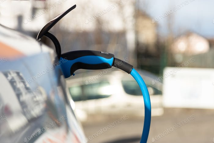 EV electric car pluged charging at a recharge station in the city