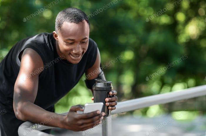 Smiling african sporty guy chatting on phone, drinking protein
