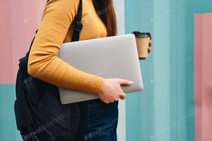 Close up casual student girl standing with laptop and coffee to go over colorful background