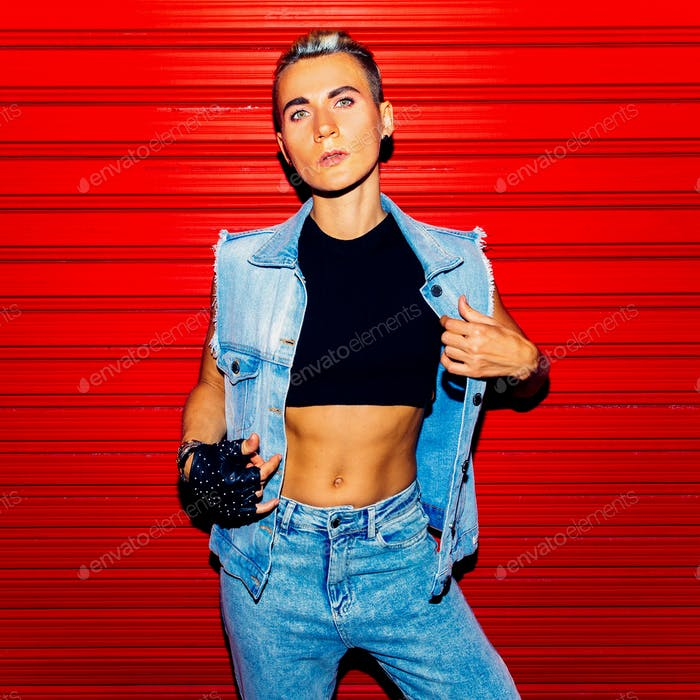Stylish Tom boy model in jeans outfit on a red background. Stree