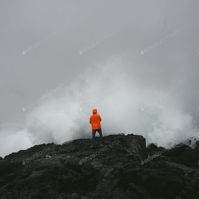 Man facing fierce wave on volcanic rocks.